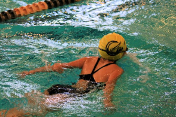 Kailyn at swim meet performing butterfly stroke
