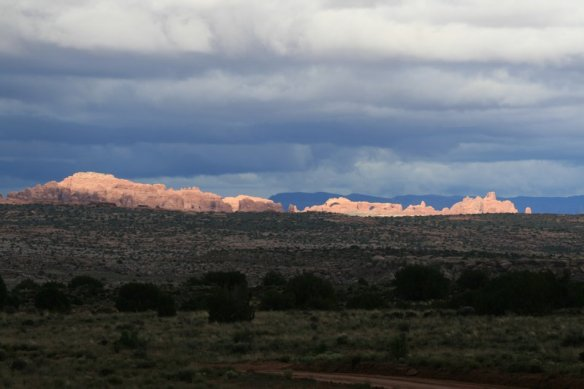 The Sun Peeks Through the Clouds to Light Arches National Park (view from our camp)