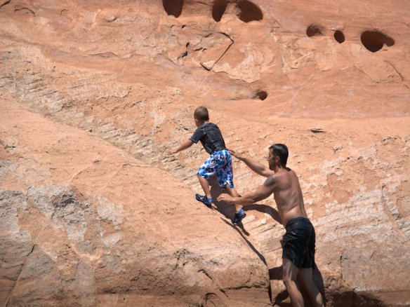 Sean helps 6-year-old Brady climb up for a cliff jump.